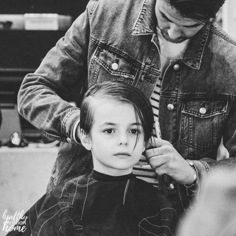 Little boy sitting in a salon chair getting a haircut.
