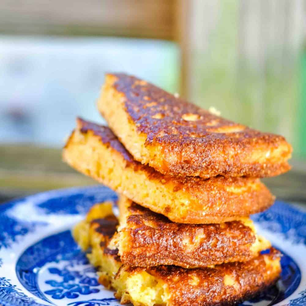 Crispy southern cornbread on a blue willow plate.