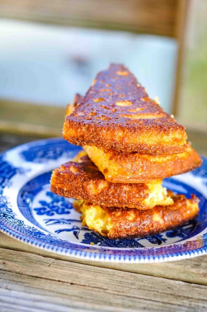 best cornbread recipe slices stacked on a blue willow plate.