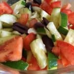 Tomato cucumber onion salad in a large glass bowl.