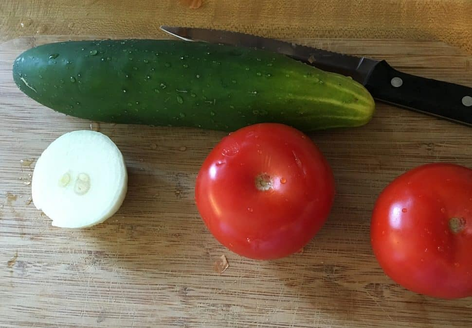 Cucumber salad prep - a large cucumber, two tomatoes, and half an onion rest on a wooden cutting board.