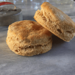 Two golden homemade biscuits on a marble platter - mastering baking is great for learning how to save money.
