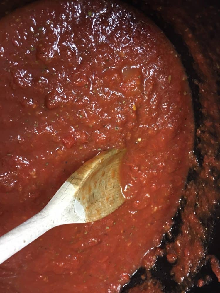 Homemade spaghetti and meatballs marinara sauce in a slow cooker with a wooden spoon.