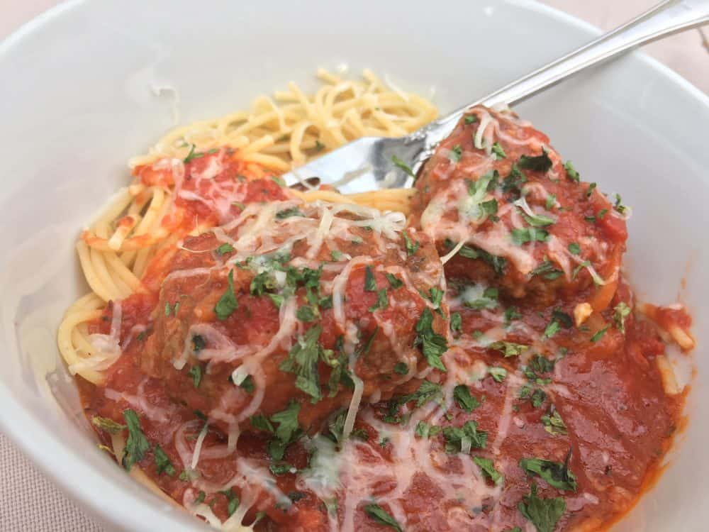 Spaghetti and meatballs with parsley in a white ceramic bowl.