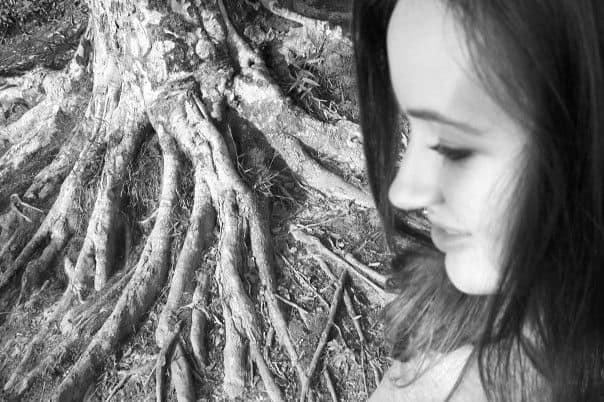 Black and white photo of a Christian wife in profile, next to a large tree root system.