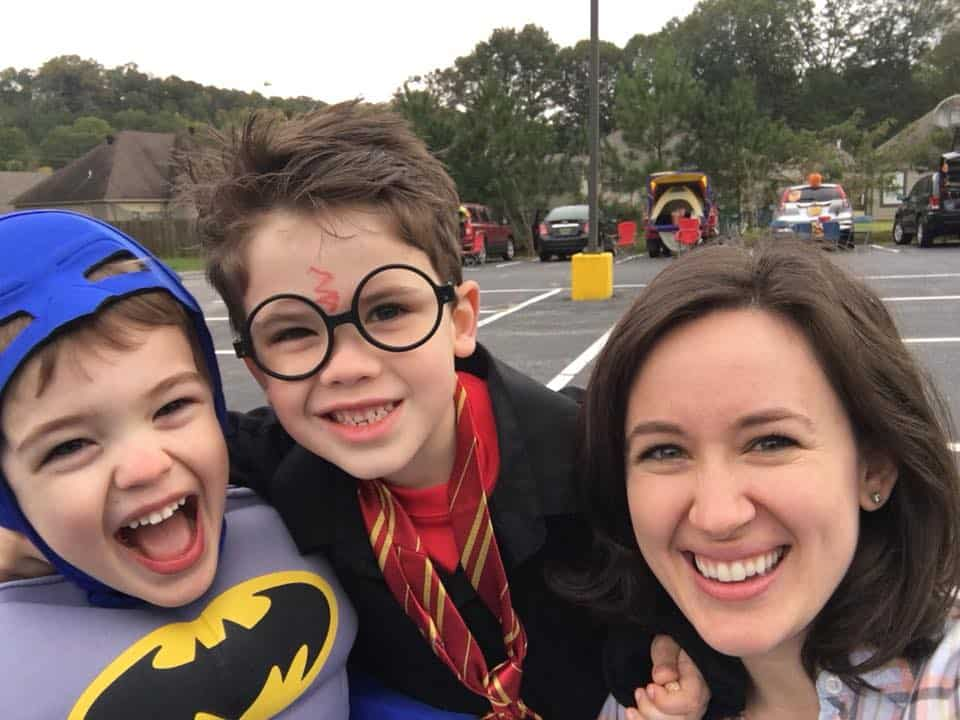 Two sons dressed up for halloween, smiling with their mother.