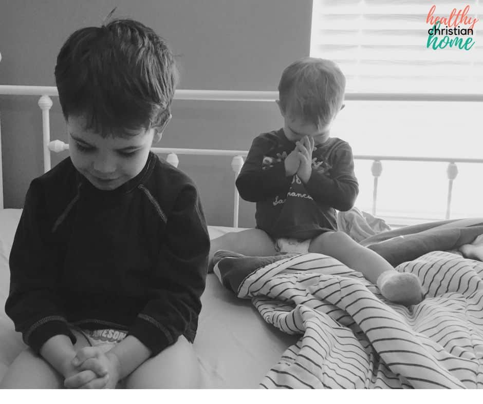Black and white photo of two little boys praying.