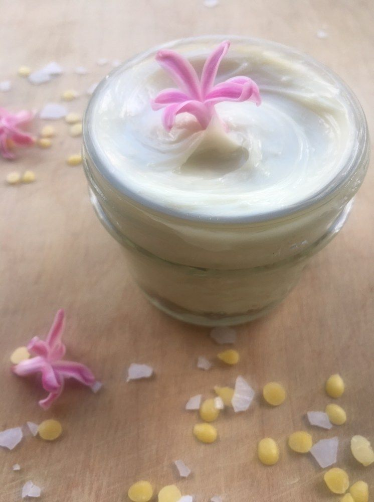 DIY magnesium lotion in a jar with pink flowers, beeswax, and magnesium flakes surrounding.