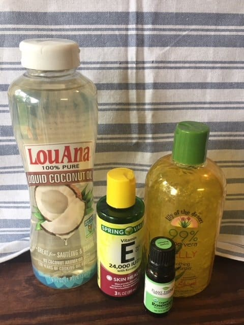 Natural DIY body lotion ingredients lined up on a wooden surface: coconut oil, vitamin E, aloe, and essential oil.