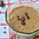 Homemade chocolate smoothie in a small glass, garnished with cacao nibs.