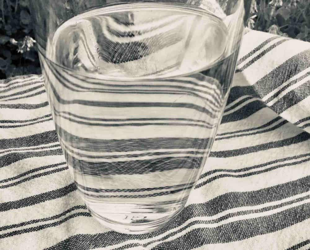 Glass of water on a striped tea towel