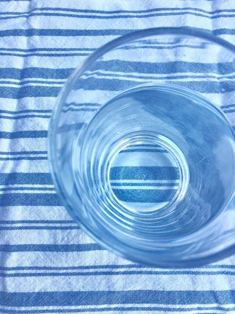 How much water should I drink? A glass of water on a striped tea towel.