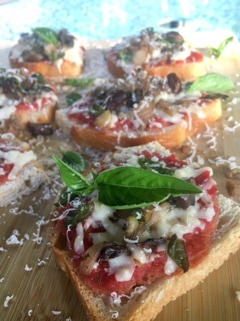 Sourdough mini pizzas on a board and garnished with parmesan and fresh basil.