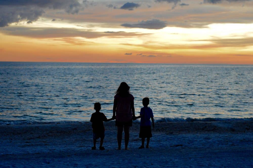 proverbs 31 woman overlooking the ocean at sunset with her two children