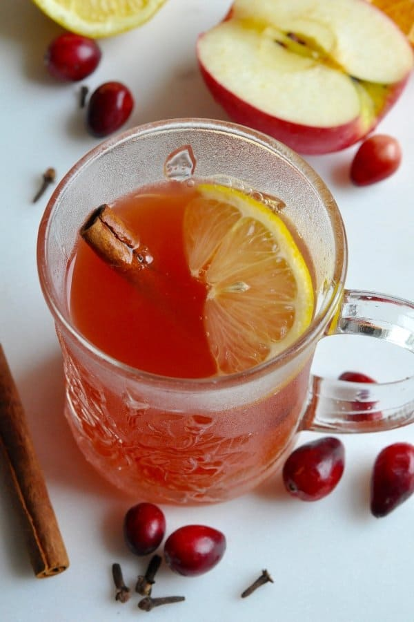 Healthy cranberry wassail in a cup garnished with cinnamon and a lemon wedge.