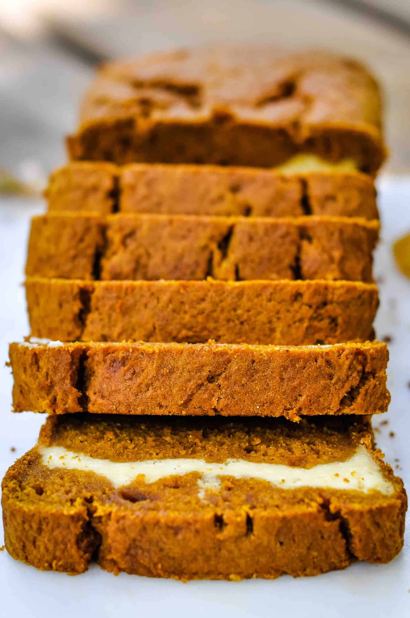 Pumpkin cream cheese bread sliced on a marble tray.