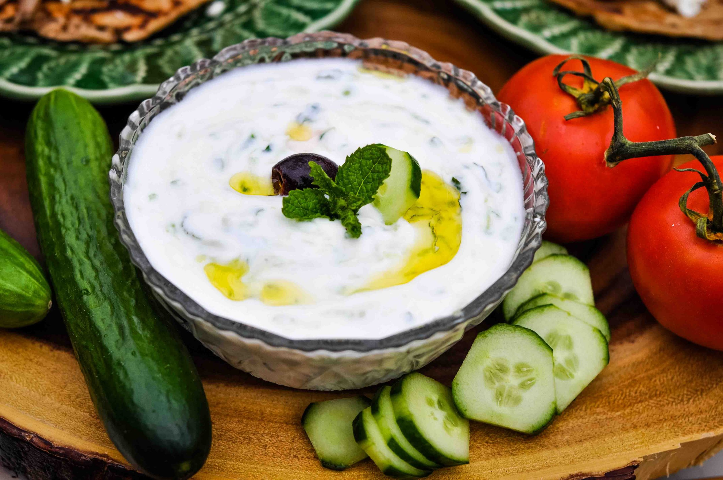 Bowl of tzatziki cucumber sauce topped with mint.