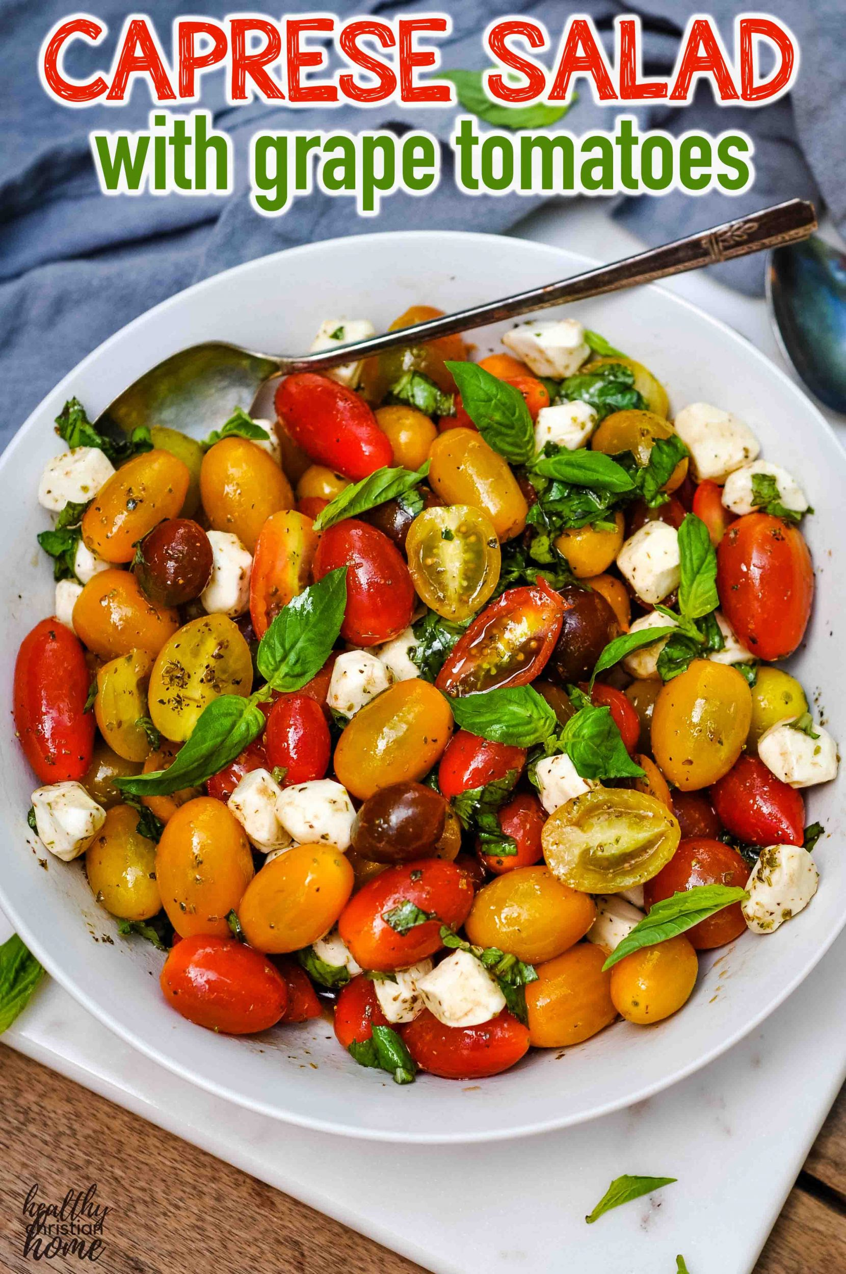 Caprese salad with grape tomatoes in a large bowl.